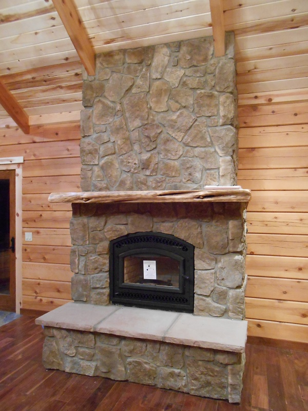 in this floor to ceiling rock fireplace with custom mantle